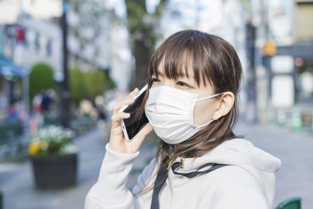 マスクをつけたままスマートフォンで通話する女性 | 10カラットの新しい面接様式 | 高級交際クラブTen Carat「10カラットブログ」